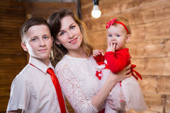 Mom with two children. Of twelve years and eleven months of age in the room stock image