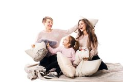 Mom and two daughters happily beat pillows and laugh. Family isolated on white background Royalty Free Stock Images