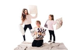 Mom and two daughters happily beat pillows and laugh. Family isolated on white background Stock Photos