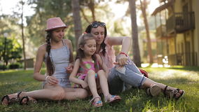 Mom with two daughters in the nature sitting on the grass and communicating through video communication using a phone stock footage