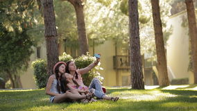 Mom with two daughters in the nature sitting on the grass and making a selfie with a phone stock video footage