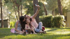 Mom with two daughters in the nature sitting on the grass and making a selfie with a phone stock footage