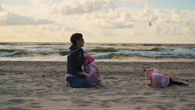 Mom and two daughters are playing on the sand at the beach at sunset. In the summer stock video footage