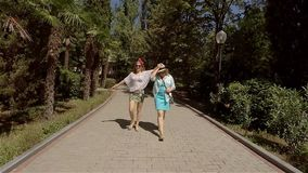 Mom and two daughters walking in beautiful green Park. Crimea stock footage