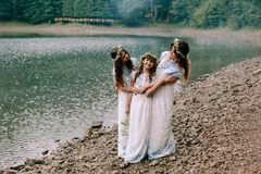 Mom and two daughters walking near the lake . Stock Images