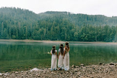 Mom and two daughters walking near the lake . Royalty Free Stock Images