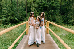 Mom and two daughters walking near the lake . Stock Photos