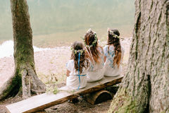 Mom and two daughters walking near the lake . Stock Image