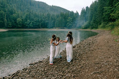 Mom and two daughters walking near the lake . Royalty Free Stock Image
