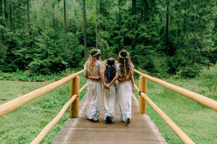 Mom and two daughters walking near the lake . Royalty Free Stock Photo