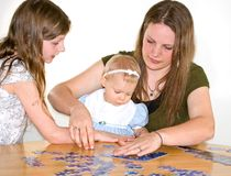 Mom and Two Girls Doing Jigsaw Puzzle. This mom and 2 girls are putting together a jigsaw puzzle on a table for family time Stock Image