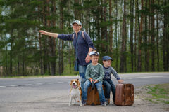 Mom with two kids and a dog stop the car. Mum with suitcases, two children and dog, the Beagle stops a passing car on a highway Royalty Free Stock Photos