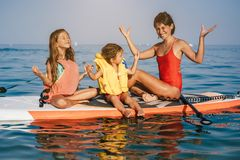Mom and two little daughter doing yoga on the paddle board. At sea stock image