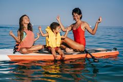 Mom and two little daughter doing yoga on the paddle board. At sea royalty free stock photography