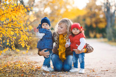 Mom and two little girls walking in the Park in autumn Stock Photos