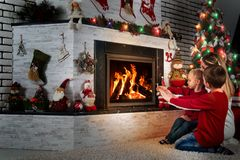 Mom and two little sons sit and relax under a Christmas tree by the fireplace,warm their hands by the fire. Merry Christmas and Happy Holidays Stock Photo