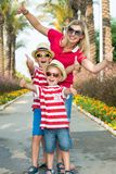 Mom and two son in sunglasses and hats to walk through the alley of palm trees.Family summer vacation. stock photo