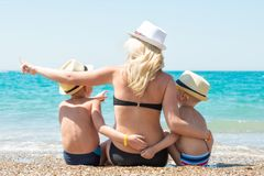Mom and two sons in hats sitting on the beach and looking at the sea. stock images