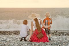 Mom and two sons sitting on the beach and watching the waves. View from the back Royalty Free Stock Photos