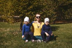 Mom with two sons sitting on the grass in the Park stock photo