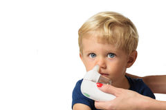 Mom using kids electric nasal aspirator. Mother using baby electric nasal aspirator. She is doing a mucus suction to twenty months baby boy,white backgrounds Royalty Free Stock Photos