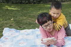 Mom using smartphone with kid watching. Chinese mom using smartphone on lawn, kid riding on back watching Stock Photo