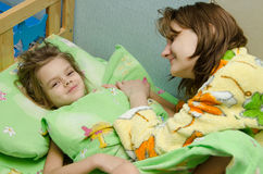 Mom wakes up her daughter in the morning stock images