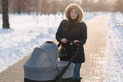 Mom walk with baby in pram. Winter park. Happy woman with her baby royalty free stock photos