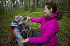 Mom walks in the forest with a child, a child in the children carry. Stock Images