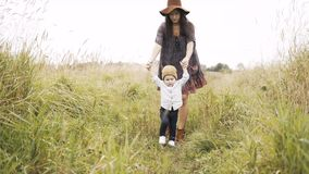 Mom walks with her little son in the field stock video footage