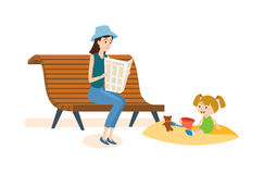 Mom walks in the park with her daughter and reading. Kids on the playground concept. Mom walks in the park with her daughter and reading a newspaper on a bench Royalty Free Stock Image