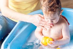 Mom washing cute boy in a blue bath. Child is bathing with a yellow duck. Hygiene and water treatment with the baby. Mother washing little boy in a blue bath stock photography