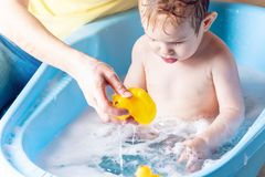 Mom washing cute boy in a blue bath. Child is bathing with a yellow duck. Hygiene and water treatment with the baby. Mother washing little boy in a blue bath royalty free stock photography