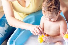 Mom washing cute boy in a blue bath. Child is bathing with a yellow duck. Hygiene and water treatment with the baby. Mother washing little boy in a blue bath royalty free stock photos