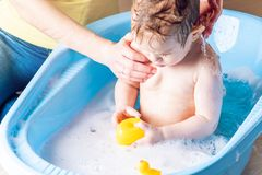 Mom washing cute boy in a blue bath. Child is bathing with a yellow duck. Hygiene and water treatment with the baby. Mother washing little boy in a blue bath stock photos