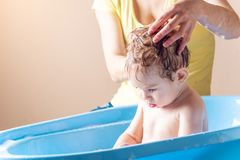 Mom washing head and hair little boy in a blue bath. Hygiene and water treatment at home with the baby stock photo