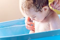 Mom washing head and hair little boy in a blue bath. Hygiene and water treatment at home with the baby royalty free stock image