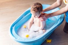 Mom washing little boy in a blue bath in the bathroom. Baby playing with a yellow duck and soap bubbles royalty free stock photo