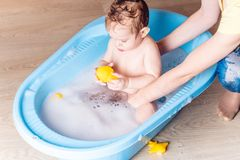 Mom washing little boy in a blue bath in the bathroom. Baby playing with a yellow duck and soap bubbles. Mom washing little boy in a blue bath in the bathroom stock images
