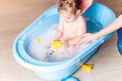 Mom washing little boy in a blue bath in the bathroom. Baby playing with a yellow duck and soap bubbles. Mom washing little boy in a blue bath in the bathroom stock image
