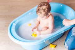 Mom washing little boy in a blue bath in the bathroom. Baby playing with a yellow duck and soap bubbles stock images