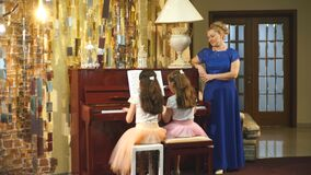 Two beautiful girls play the piano. Mom watches her daughters play the piano, slow motion stock video footage