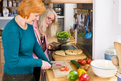 Mom Watching her Other Friend Preparing Food Stock Photo