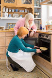 Mom Watching Other Mom Putting Cake in an Oven Royalty Free Stock Photography