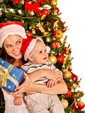 Mom wearing Santa hat holding  baby  under Royalty Free Stock Image