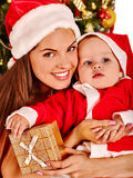 Mom wearing Santa hat holding  baby  under Stock Photos
