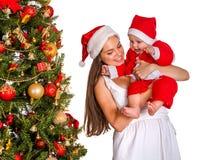 Mom wearing Santa hat holding baby under Christmas tree. Royalty Free Stock Photo