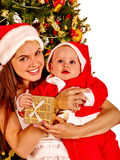 Mom wearing Santa hat holding baby under Christmas tree. Royalty Free Stock Images