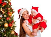 Mom wearing Santa hat holding baby under Christmas tree. Stock Image