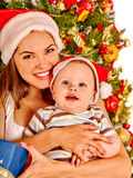 Mom wearing Santa hat holding  baby  under Stock Photography